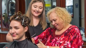 A cosmetology instructor inspects a student's work on a client's hair