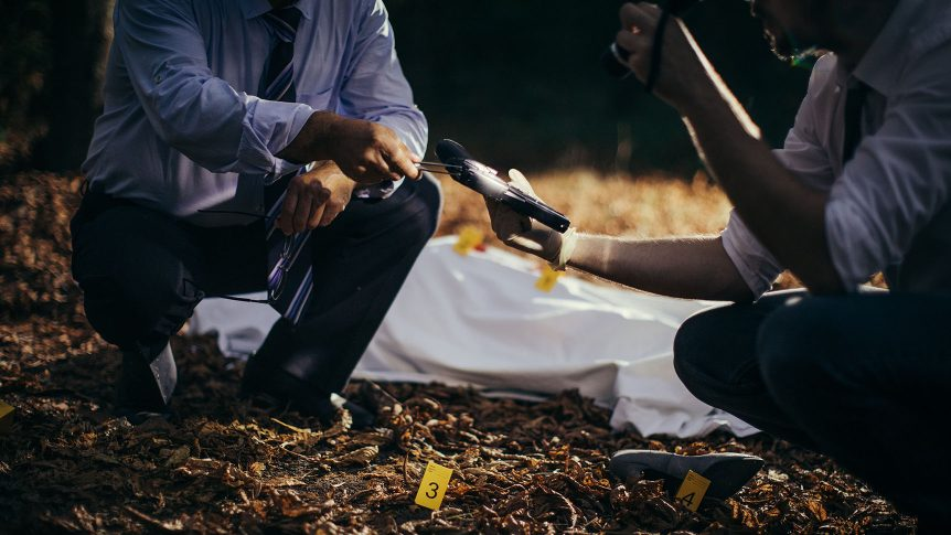 Two investigators on a crime scene investigation with a covered body, a shoe and a gun in the forest.