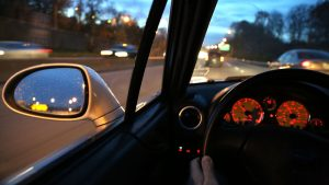 Dashboard view of a moving vehicle at dawn on a busy divided highway
