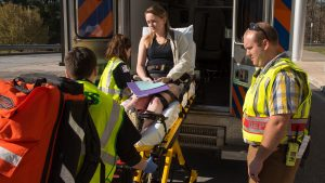 two e m s students load a patient in an ambulance with an instructor looking on