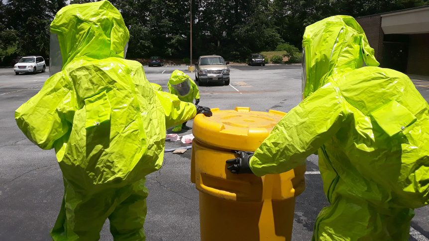 two people in haz mat suits wheel a plastic drum toward a spill another person in a haz mat suit is cleaning up