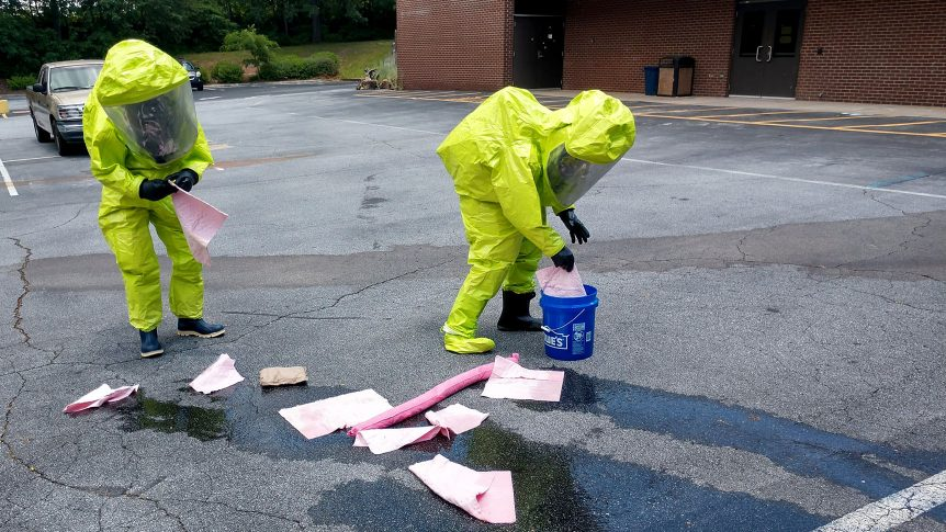 two students in hazardous materials suites clean up a spill