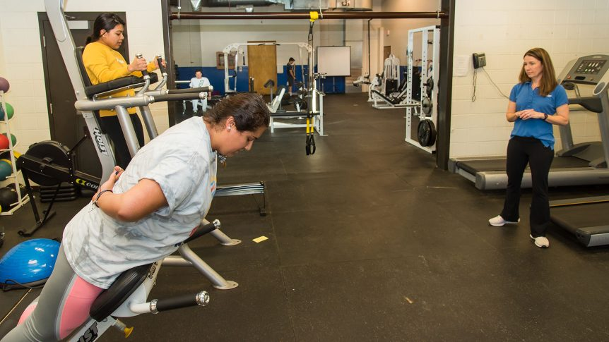 Two female students work out in the on-campus fitness room while an instructor looks on
