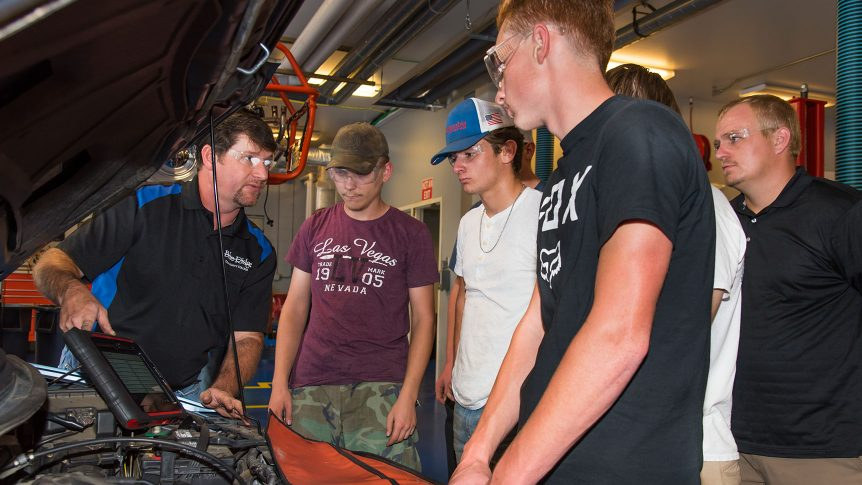 a group of students stand around the open hood of a car while an instructor explains a diagnostic tool to them
