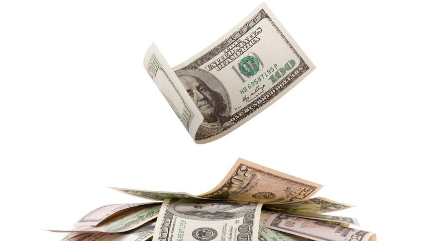 hundred dollar bill falling onto pile of money