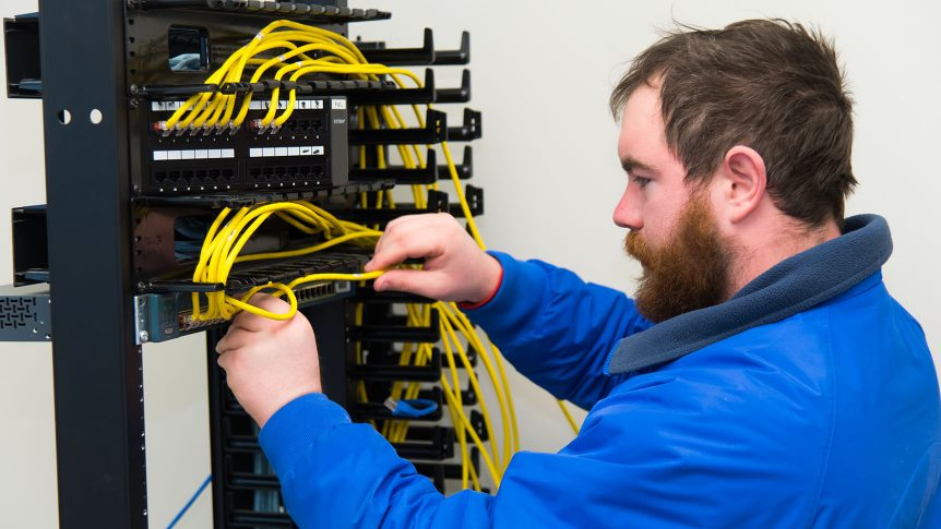 A student wiring a network switch