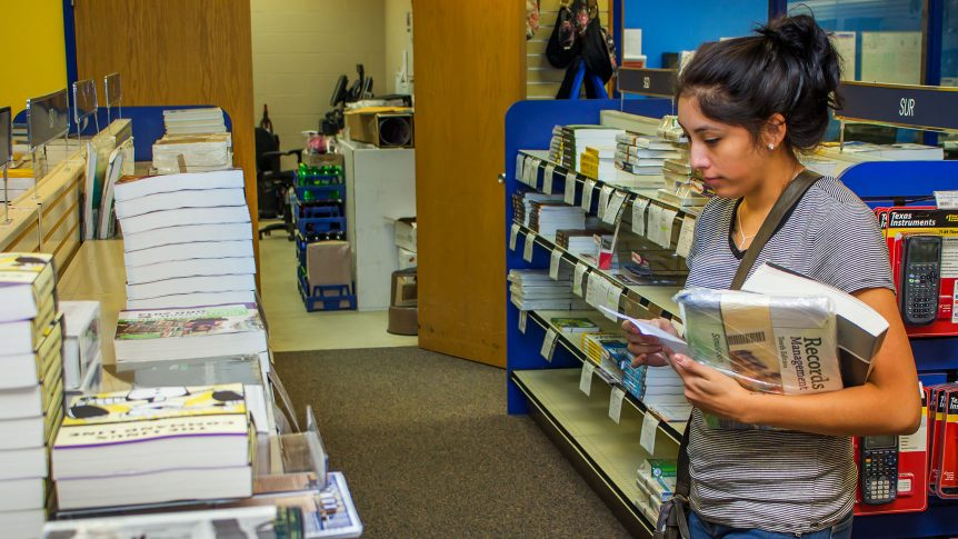 a students looks for her textbooks in the campus bookstore