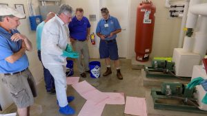 a man in protective coveralls with booties and gloves cleans up a spill in a utility room with four others looking on