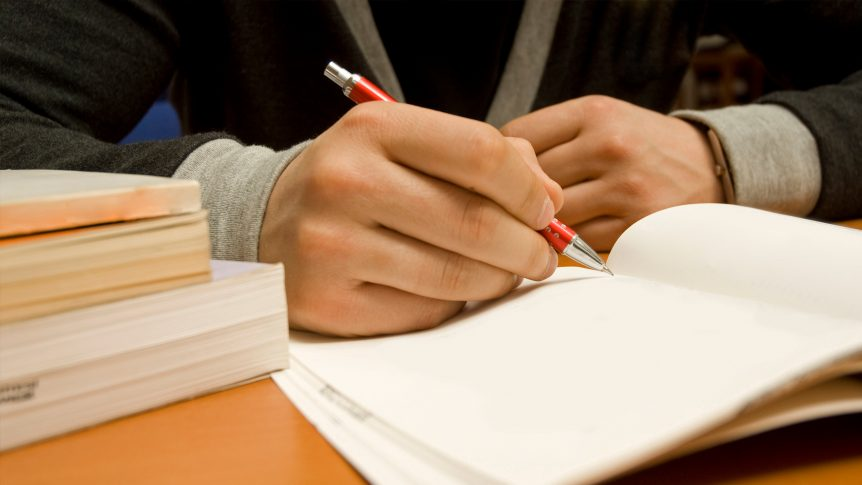 student hand holds pen and writes in notebook; books nearby