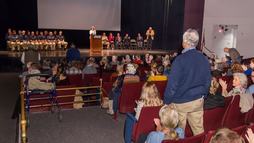 A group of people on stage sit before an audience in Thomas auditorium