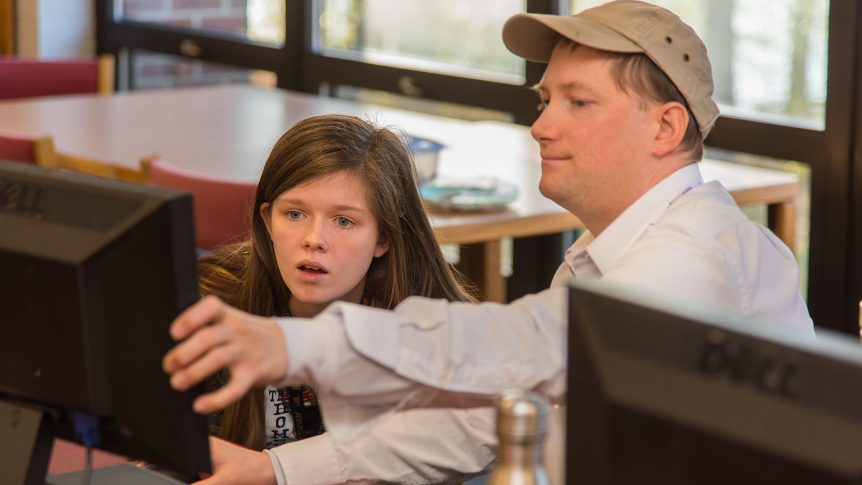 A student looks at a computer monitor that an adviser is pointing to