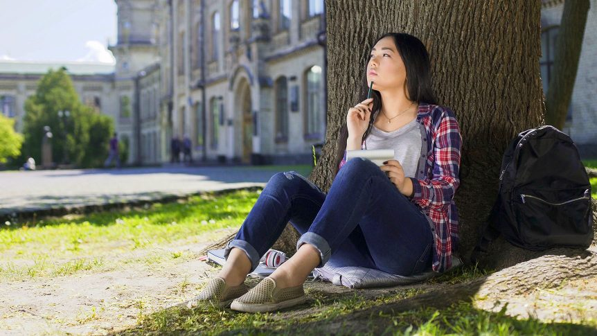 student sitting under tree on a college campus, holding notebook, thinking