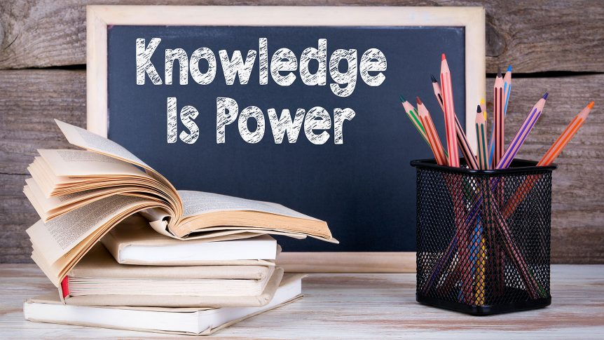 chalk blackboard with Knowledge is power written on it, a stack of books and pencils in front of it on the wooden table