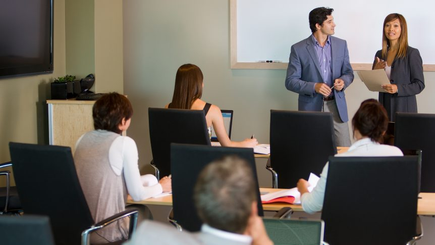 two business people leading a workshop or class in front of a group