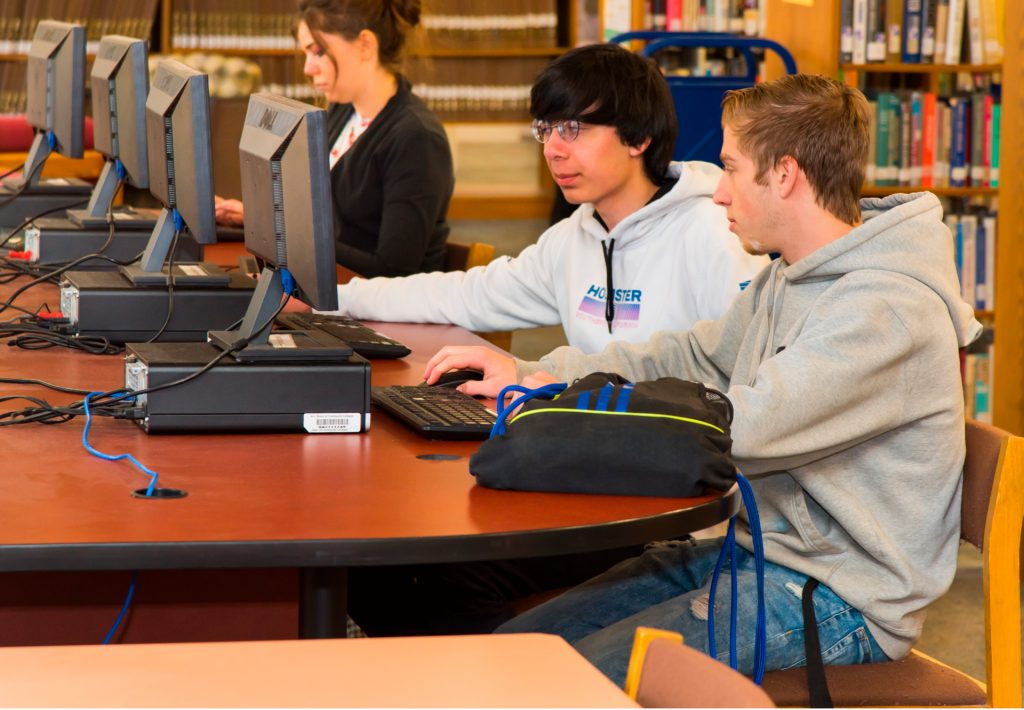 three students at computers in the library
