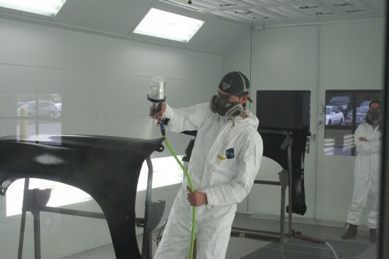 Male and female student painting a car
