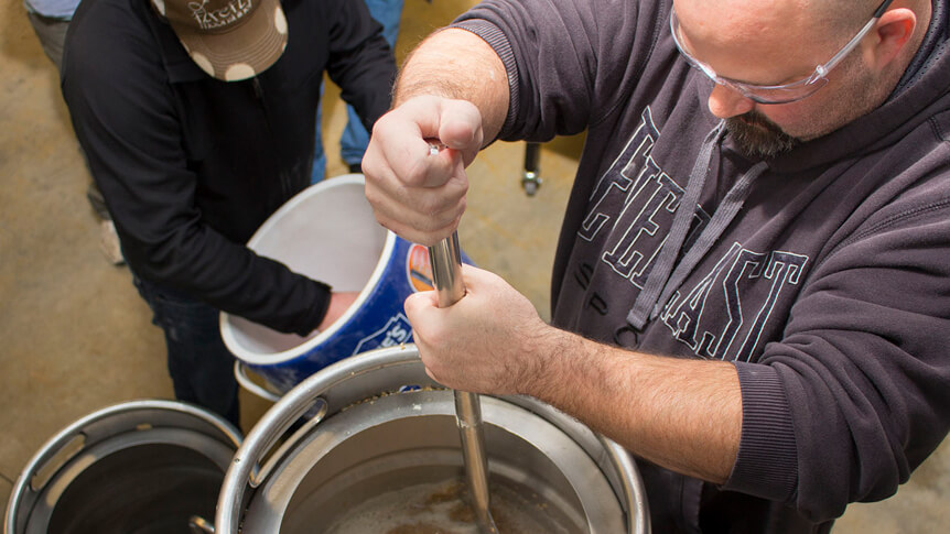 student stirs mixture in brewing kettle