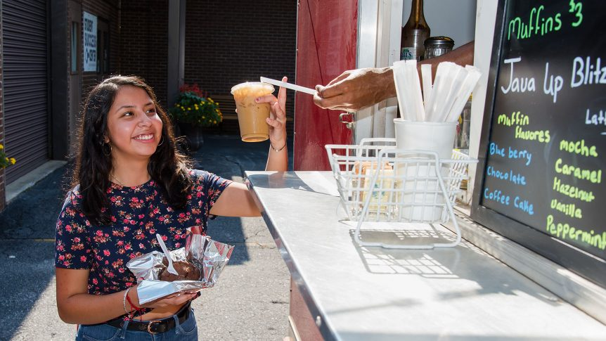 smiling student holds coffee and food in front of a food truck