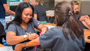Phlebotomy students practice learning preparation to draw blood