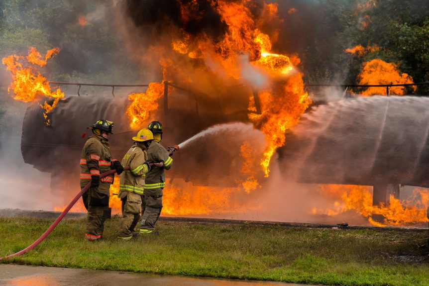 Three firefighters putting out a burning tanker