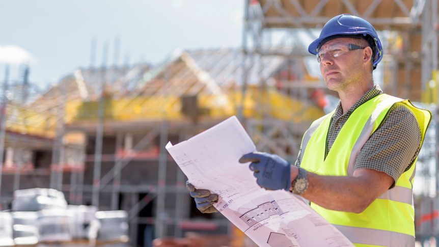 man in protective gear hard hat, gloves holds blueprint and looks at construction site