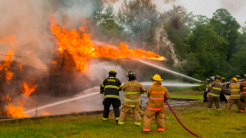 fire personnel at a training with hoses work to put out a large burning fire