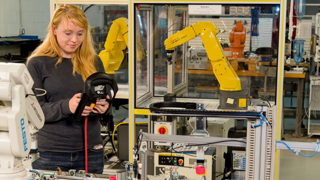 Female engineering student works on mechatronics equipment