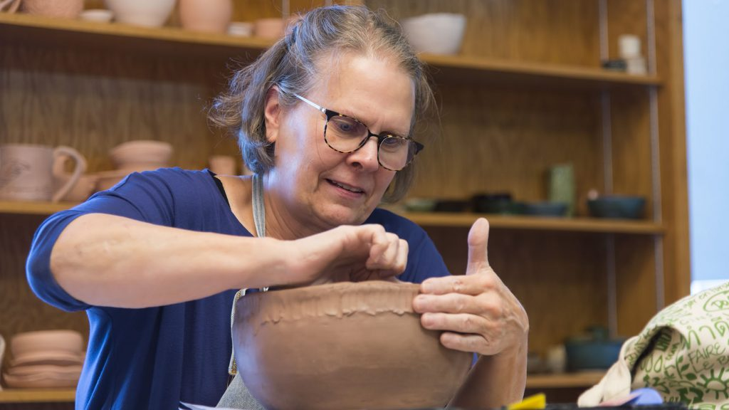 Pottery student works on a clay pot