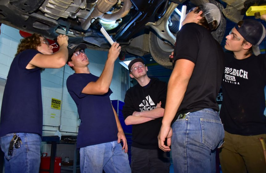 Young men working on the underside of a car