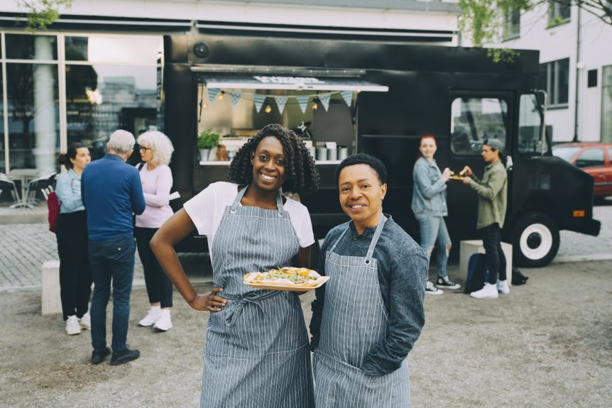 Group of people standing outside a food truck