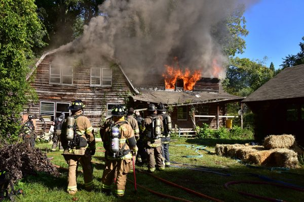 Group of firefighters approaching a burning cabin