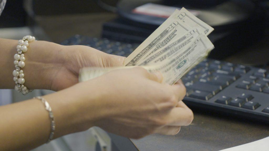 hands with twenty-dollar bills, counting money